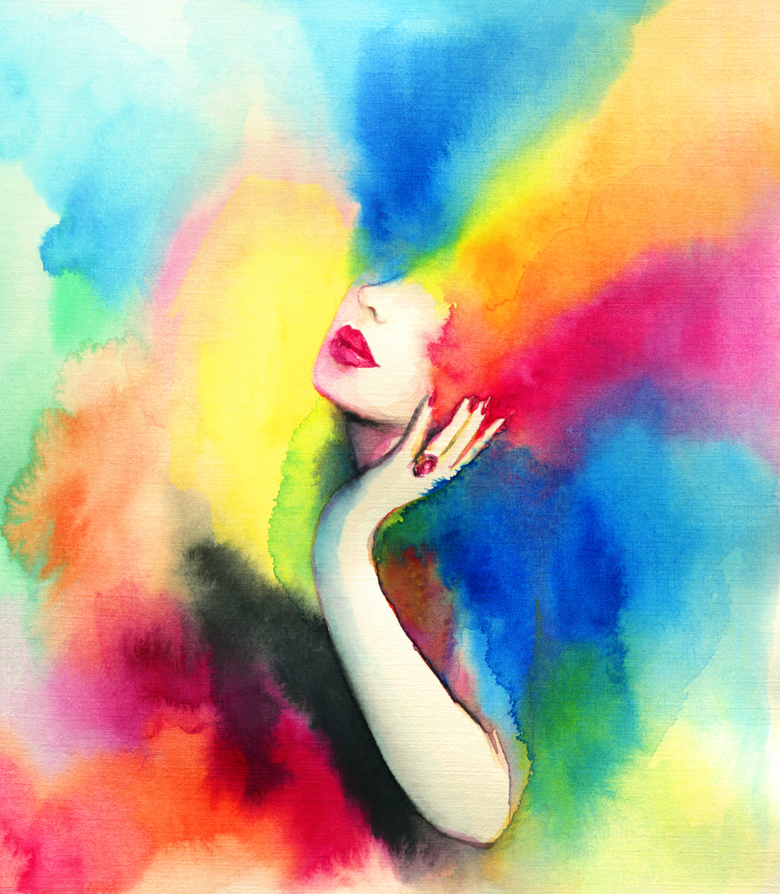 Chasing the muse: What does your ideal writing space look like? This photo shows part of a white woman's face and arm, surrounded by watercolor rainbows. Her lips are bright red, as are her painted fingernails and large ring.