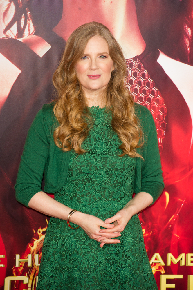 Suzanne Collins, the author writing the new Hunger Games prequel, attends a Hunger Games film premiere in an emerald-colored dress.