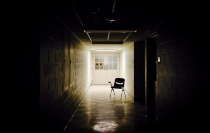 School's out: An end-of-the-school-year writing prompt. In this photo, a lone chair is silhouetted in a darkened school hallway.