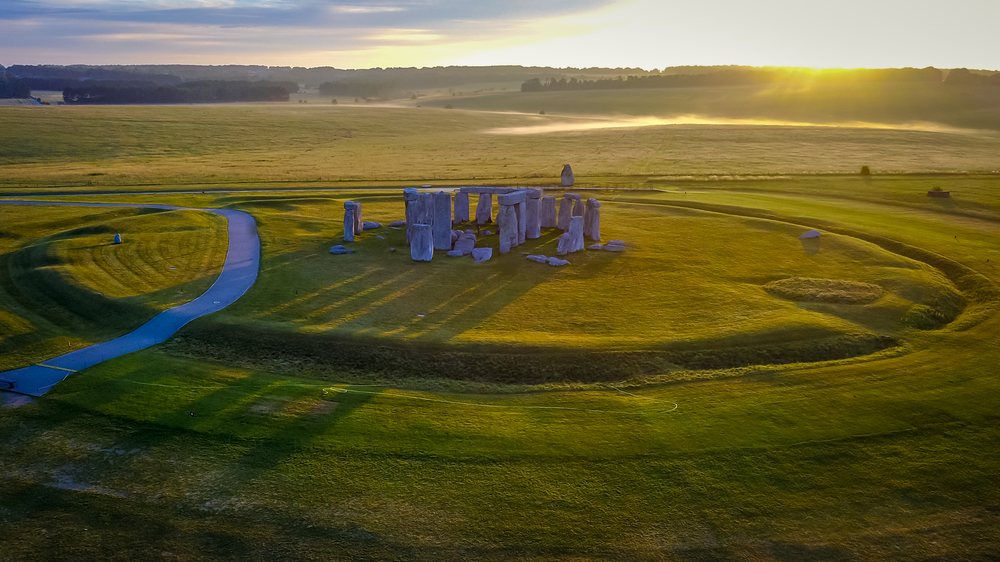 This summer solstice writing prompt asks you to imagine a world where sunlight operates differently. The photo shows Stonehenge at sunrise.