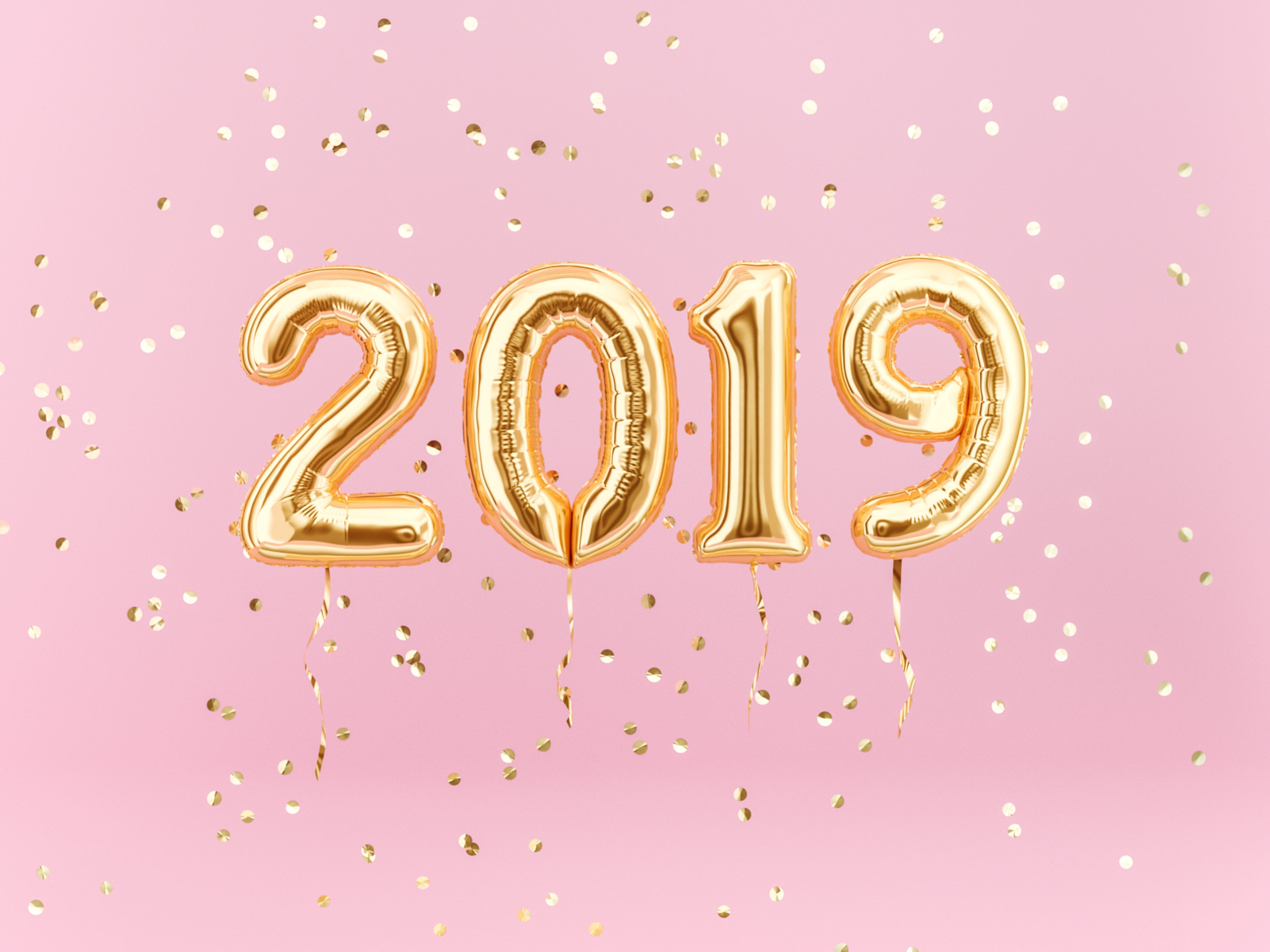 "Our favorite posts of 2019. This image features gold balloons in the shape of ""2019"" on a light pink background with gold confetti."
