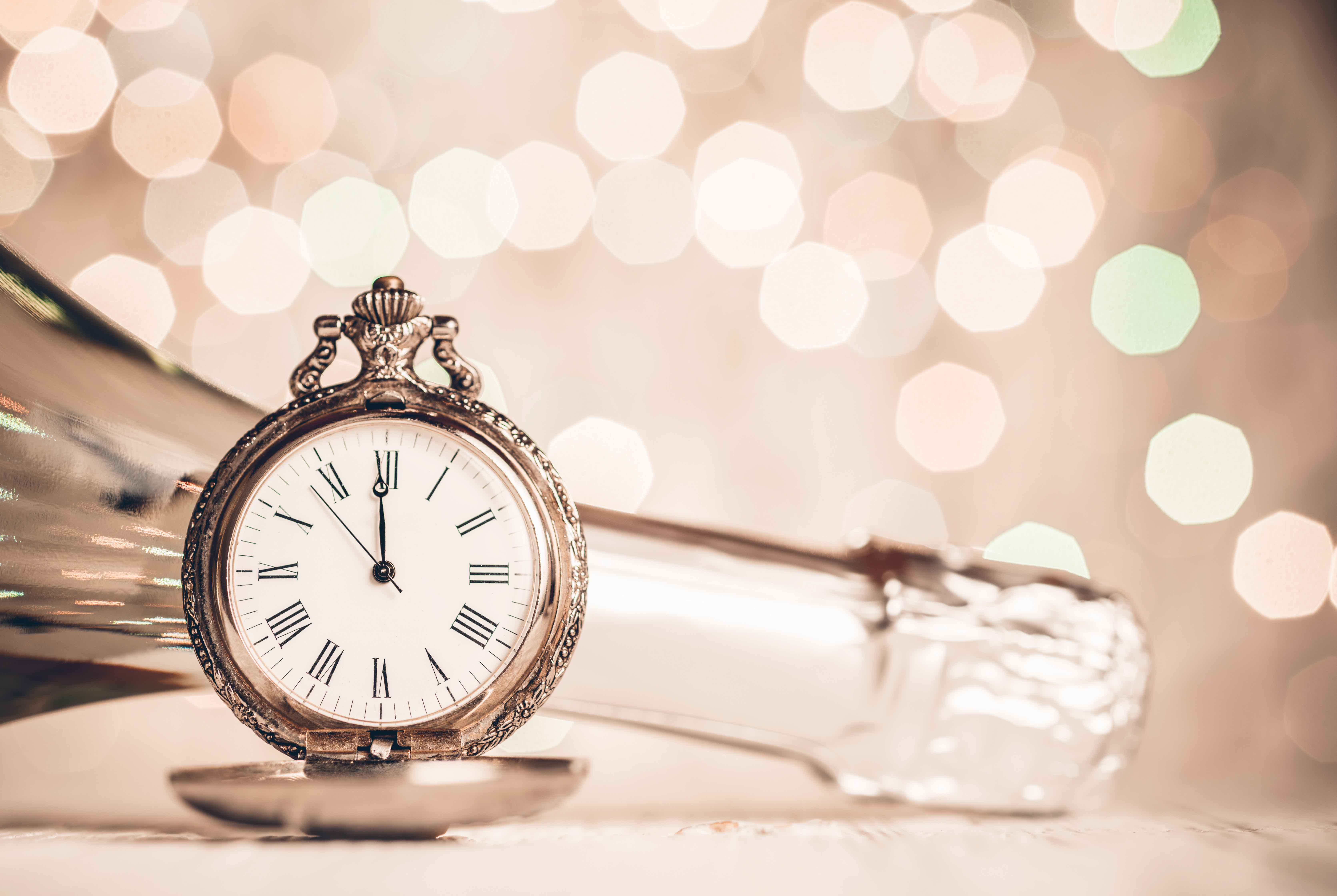Counting down our most popular writing articles of 2019. This image features a pocketwatch at 12:00 midnight along with a sideways bottle of champagne on a gold and glittering background.