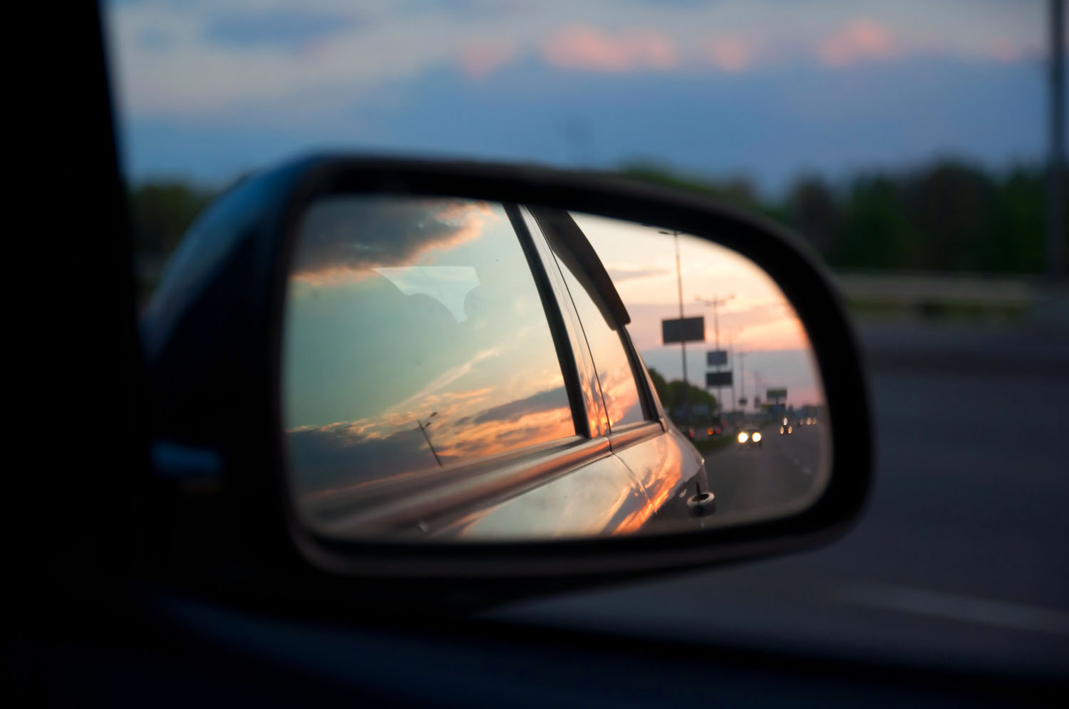 Objects in Mirror are Closer Than They Appear: How unconscious bias can affect your fiction. This image shows a side mirror of a car at sunset.