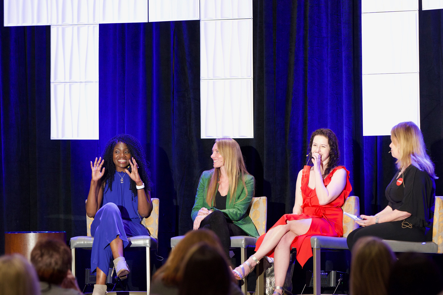Nana Malone, Meredith Wild, K.A. Linde, and moderator Karen Rawson are seated on a stage addressing the audience at a presentation during Inkers Con.