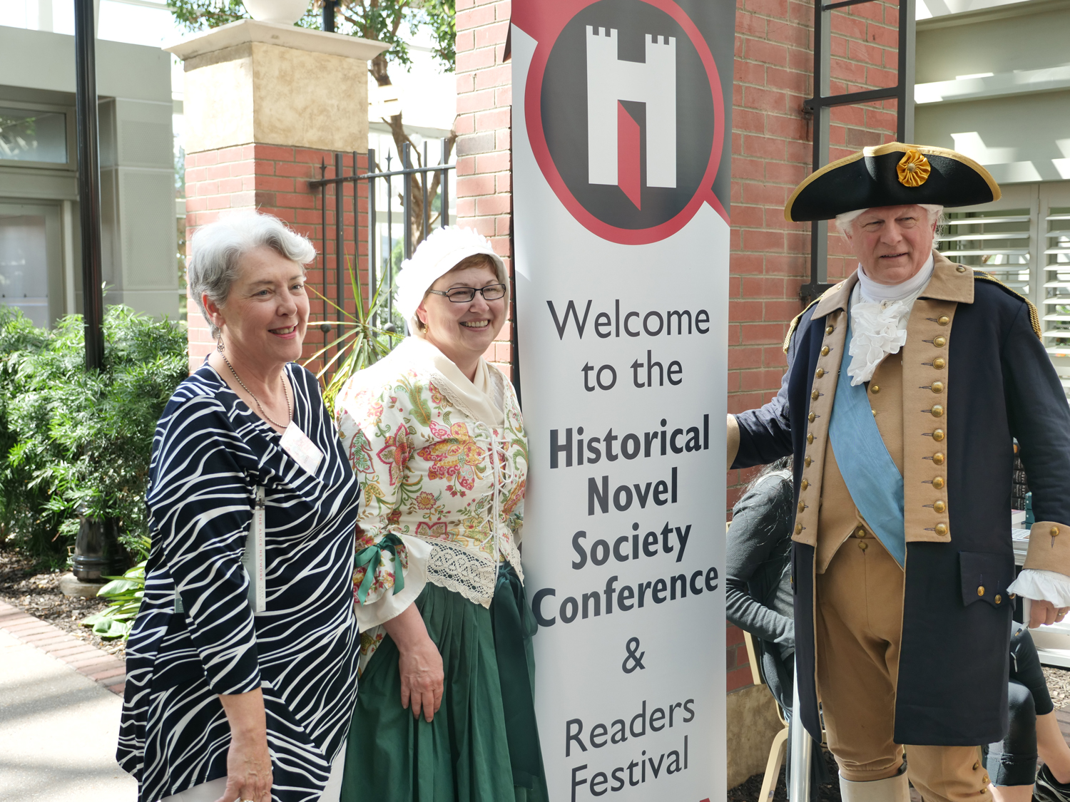 Sandy and Vern Frykholm, dressed as Martha and George Washington, greet attendees beside a sign that welcomes attendees to the Historical Novel Society Conference and Readers Festival.