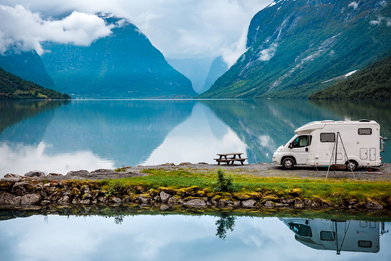 An RV is parked near a picnic table overlooking mountains and a beautiful lake.