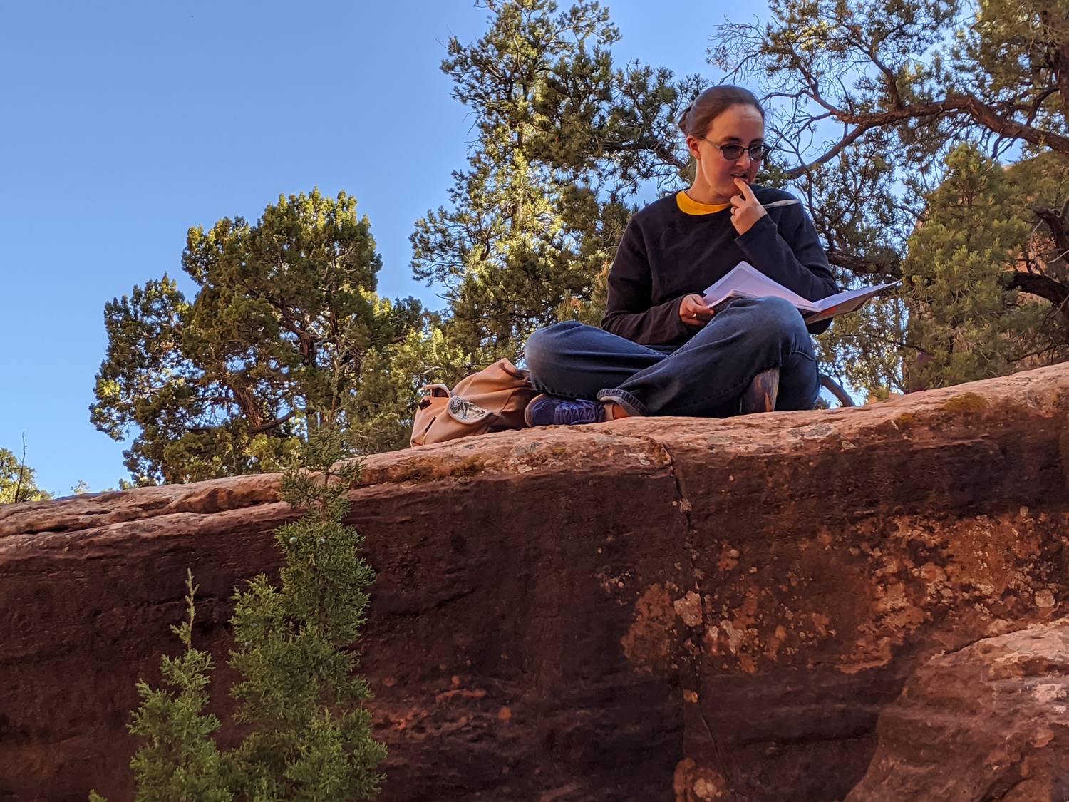 Kathryn Cunningham writes on a plein air hike at the Bunting Trail Dinosaur Tracks during the 2019 Kanab Writers Conference.